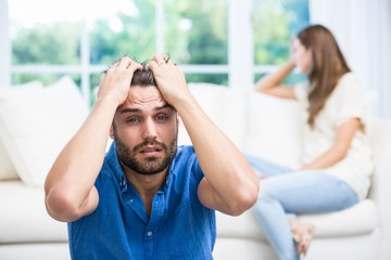 Upset man with hands on head after argument with wife