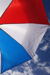 Red-White-Blue Umbrella against Partly Cloudy Sky - Umbrella dominant