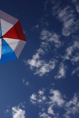 Red-White-Blue Umbrella against Partly Cloudy Sky - Sky dominant