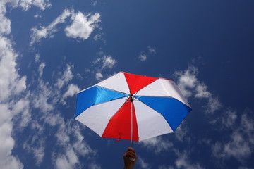 Person Holding Sunlit Red-White-Blue Umbrella under Partly Cloudy Sky
