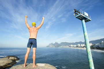 Athlete swimmer with gold swimming cap standing with his arms raised in front of the Rio de Janeiro skyline at Arpoador, Ipanema Beach