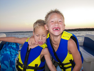 Two adorable boys on a lake at sunset.
