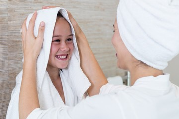 Mother drying her daughters hair with a towel