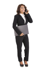 Business woman using a cellphone while holding a laptop computer
