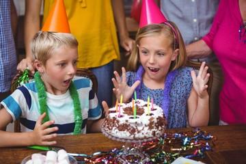 Shocked siblings with birthday cake