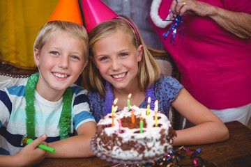 Portrait of cheerful siblings with family celebrating birthday