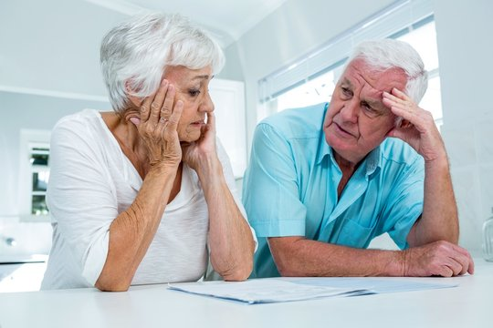 Tensed senior couple talking to each other at home