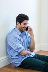 Man sitting on floor and talking on phone