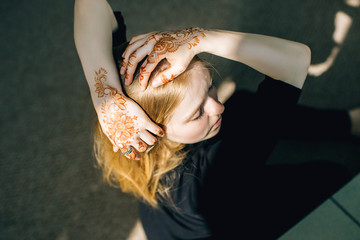 blonde girl with a pattern mhendi on her hands in the sunlight