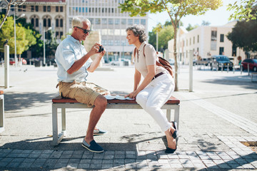 Senior tourist sitting on a bench looking pictures on camera