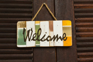 Welcome board hang on brown wooden