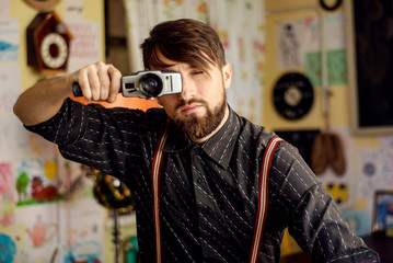 stylish hipster bearded man holding old film camera