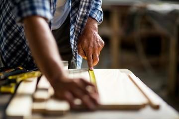 Carpenter measuring a length of wooden plank