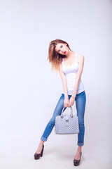 Fashion model posing on white background in the studio with a bag