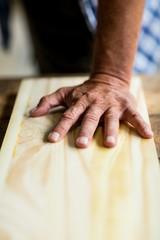 Carpenter hands measuring wooden plank