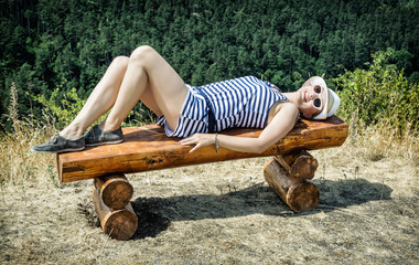 Young woman with sunhat in sailor outfit is lying on the wooden