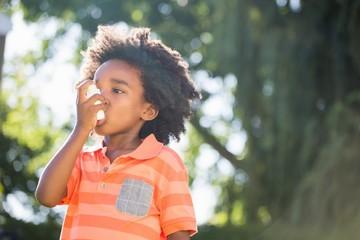 Cute mixed-race boy using a asthmatic spray