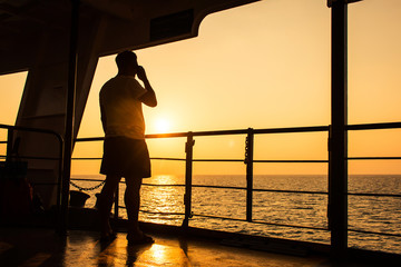 Young man use smart phone on the ship sunset background