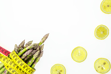 Asparagus spears with measuring tape and lemon slices, on white background with copy-space
