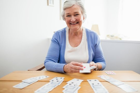 Portrait of smiling senior woman playing cards at home