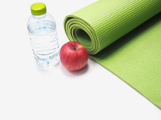 Red apple, bottle of water and yoga mat