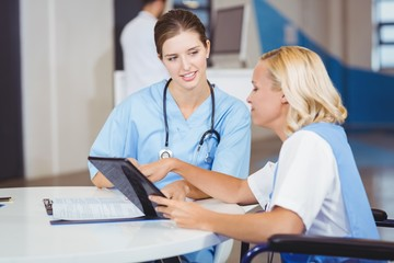 Female doctors using digital tablet while discussing