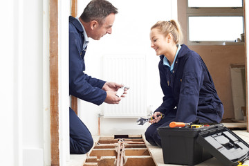 Plumber And Female Apprentice Fitting Central Heating
