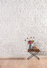 cafe table with brick wall and vase of flower
