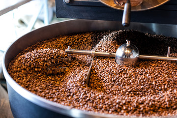 Freshly roasted coffee beans from a large roaster in the cooling cylinder. Motion blur on beans.