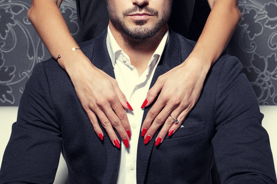 Sexy woman hands embrace rich man