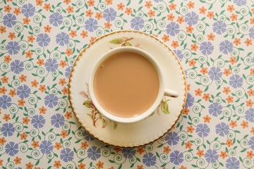 Cup of milky tea on a floral background