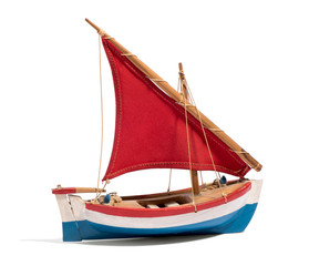 Wooden handmade toy boat with a red sail