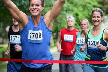 Marathon male athlete crossing the finish line