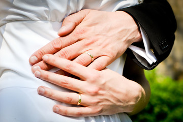 Hands of bride and groom with rings during the summer wedding.