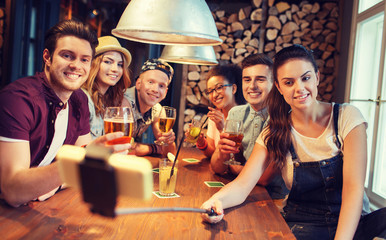 friends with smartphone on selfie stick at bar