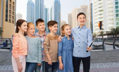 happy children with smartphone and selfie stick