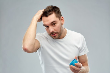 happy young man styling his hair with wax or gel
