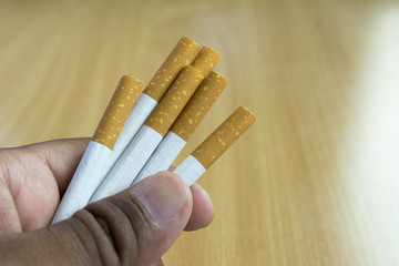 Hand hold cigarettes on wooden background