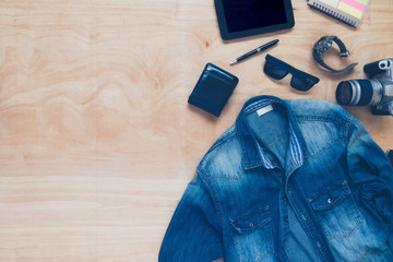 Top view of clothing and diverse personal accessory on wooden table background