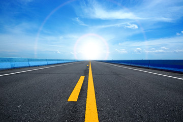 Empty road and the yellow traffic lines with blue sky.
