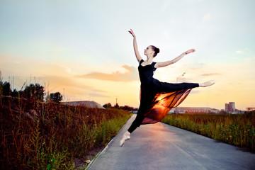 Beautiful ballerina in black skirt and leotard on street road.