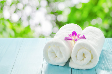 White towels roll with purple orchid flower
