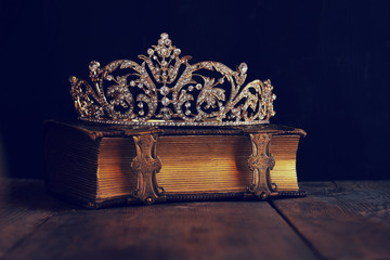 low key image of beautiful diamond queen crown on old book