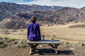 Young woman sitting on a bench and looking at a mountains with a cup of tea