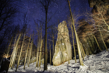 Beautiful mountain forest and big light painted rocky boulders at night in the winter. Night photography. Starry night.