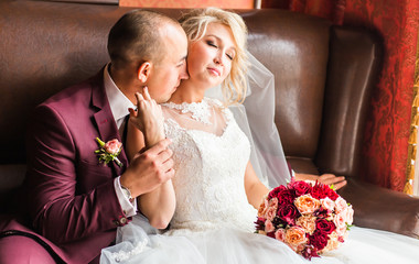 Bride and groom sitting  in a luxurious chair. Loving couple together indoors.