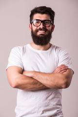 Bearded man in glasses with crossed hands look at camera on white