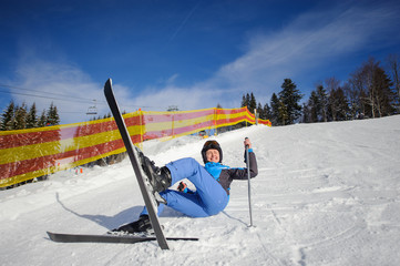 Young female skier in blue ski suit after the fall on mountain slope against ski lift and winter mountains background. Ski resort. Winter sports concept.