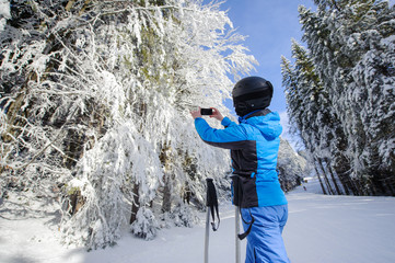 Rear view of skier in the winter forest on ski slope taking picture with her cell phone. Winter sports concept.
