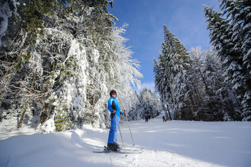Full length portrait of happy skier on a ski slope in the forest with big beautiful trees covered in snow. Winter sports concept. Bukovel, Ukraine